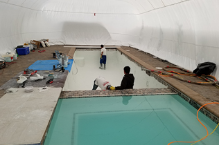 White Construction Dome - Inside view of workers touching up plaster.