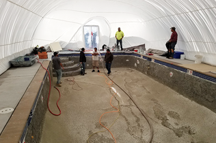 Construction Dome - Inside view of workers prepping pool area to lay plaster.