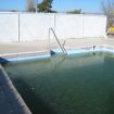Pool has green water, pool and deck need repair.
