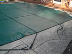 Side profile of a green solid vinyl pool cover.