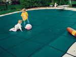 Children playing on safety pool cover